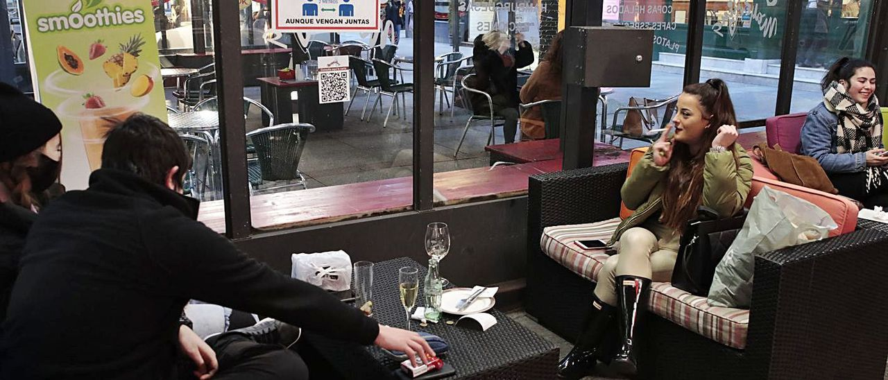 Adrián Llaneza y Claudia Tuero, con Olaya Zapico fumando en una terraza en un local de Gijón.