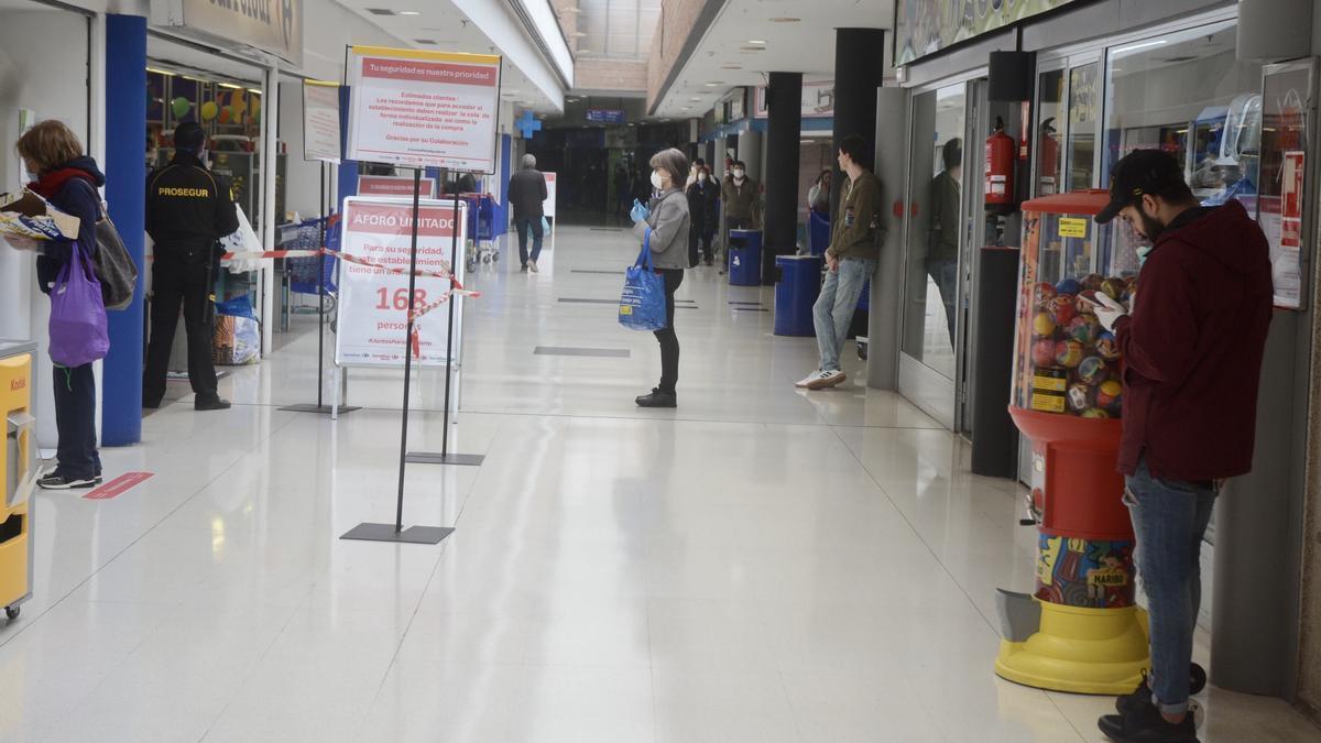 Clientes haciendo cola frente al supermercado.