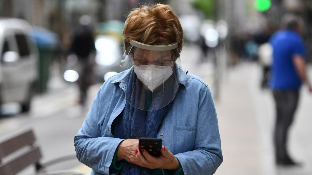 Una mujer con mascarilla y visera consultando su teléfono móvil. // Gustavo Santos