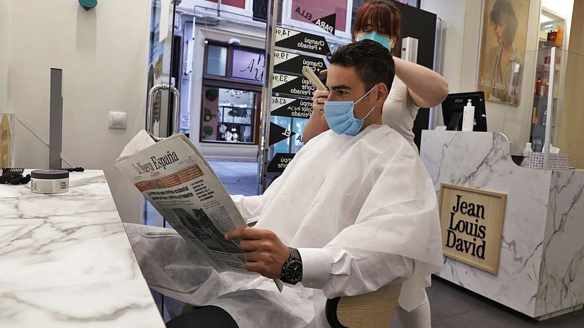 Francisco Menéndez lee LA NUEVA ESPAÑA mientras Carmen Morales le corta el pelo. | Juan Plaza