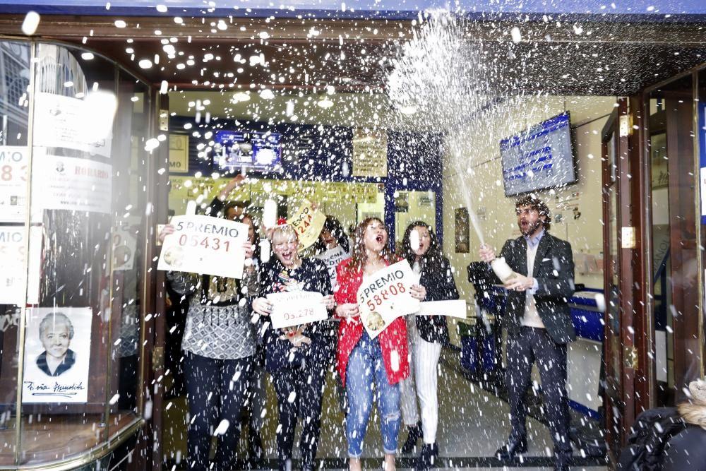 """Propietarios de la Administración de Lotería """"La Manolita"""" en la calle del Carmen en Madrid celebran el segundo premio, vendido en su administración con el número 51244, y tres quintos premios que han recaído en los números 05431, el 58808 y el 03278. EFE"""