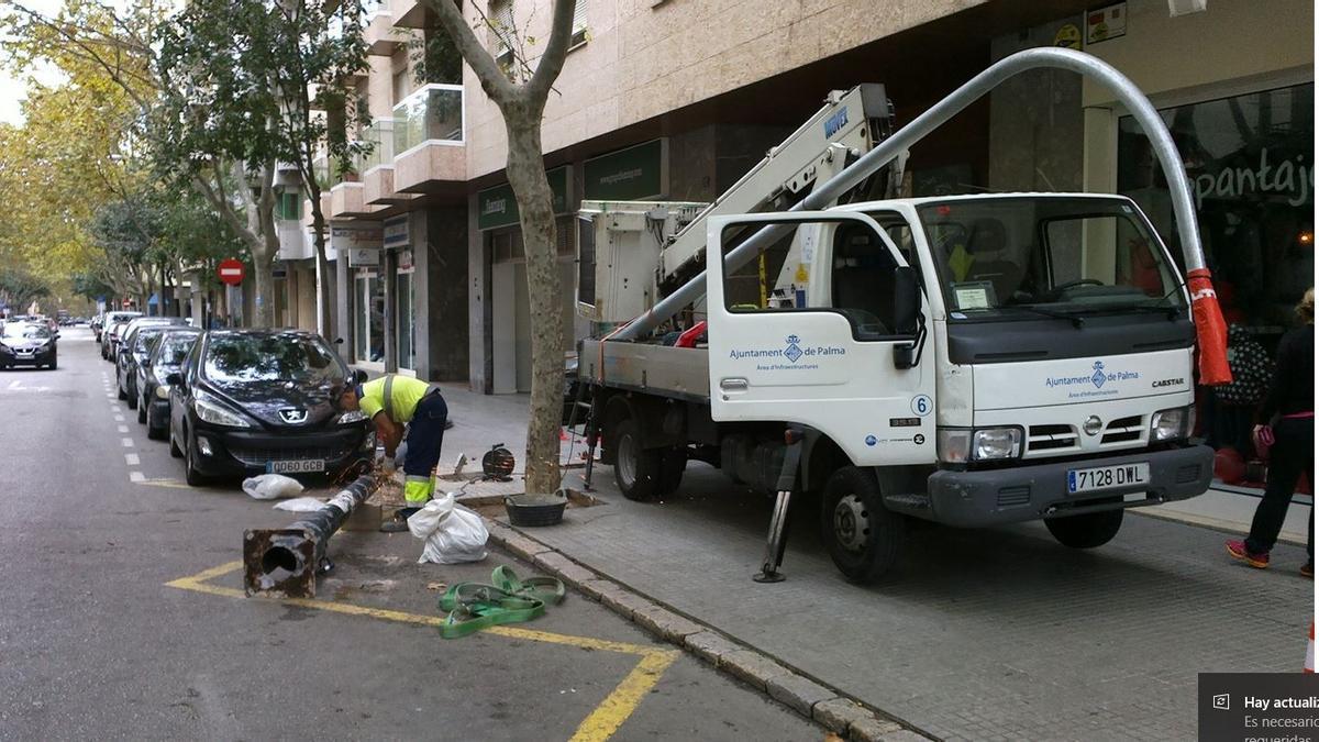 Un operario sustituye una farola en una calle de la ciudad.