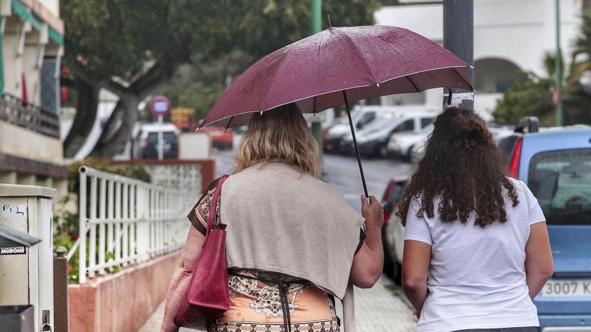 Dos mujeres, bajo la lluvia del pasado martes.