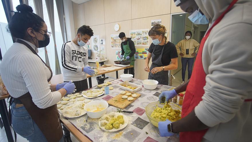 Joves migrats i no acompanyats cuinen  per gent sense sostre