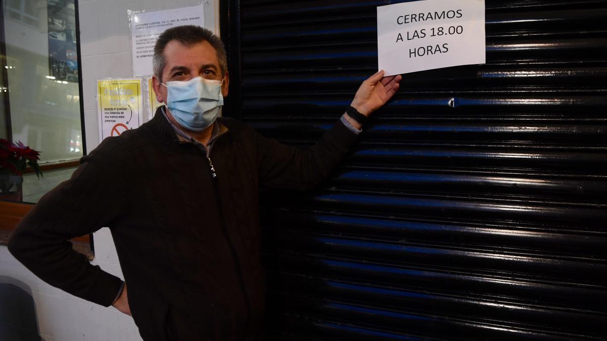 Un hostelero de la plaza del Humor muestra un cartel en su establecimiento con el horario que entrará en vigor mañana.