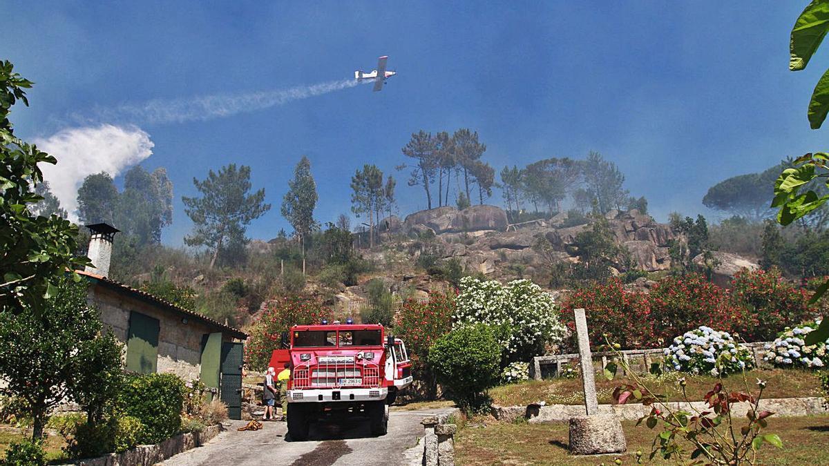 Un avión descarga sobre el foco del incendio registrado ayer en Santa Mariña.     // IÑAKI OSORIO