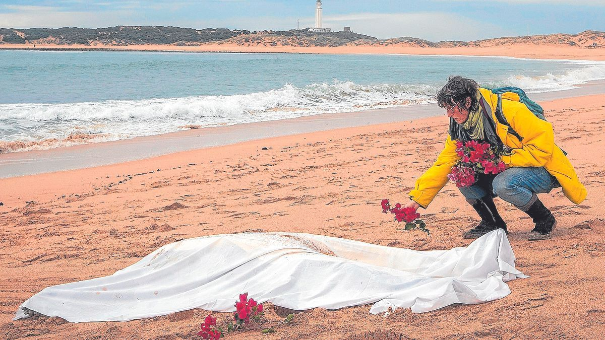 A woman places some flowers around another of the corpses found of immigrants who were shipwrecked in a boat