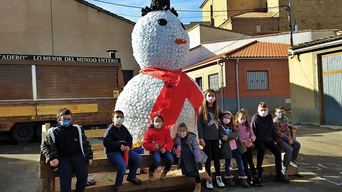 Niños y niñas del colegio de Cañizal junto al muñeco de nieve elaborado con piezas de plástico. | Cedida