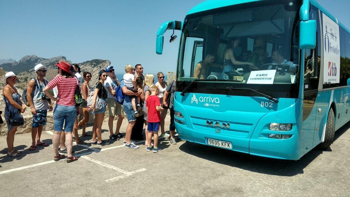 Turistas suben a un bus lanzadera en el faro de Formentor en 2018, año en el que se iniciaron las limitaciones de tráfico en la península de Pollença.