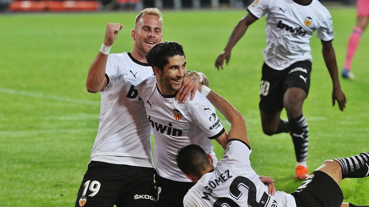 Maxi Gómez y Racic celebran el tercer gol de Carlos Soler frente al Real Madrid. | J.M.LÓPEZ
