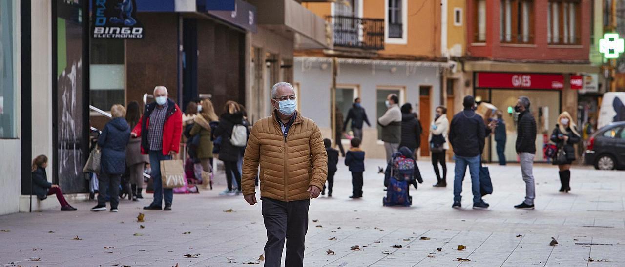 Un vecino de Xàtiva camina por la Albereda Jaume I, frente a los alumnos de Dominicas a la salida de clase, en una imagen del jueves | PERALES IBORRA
