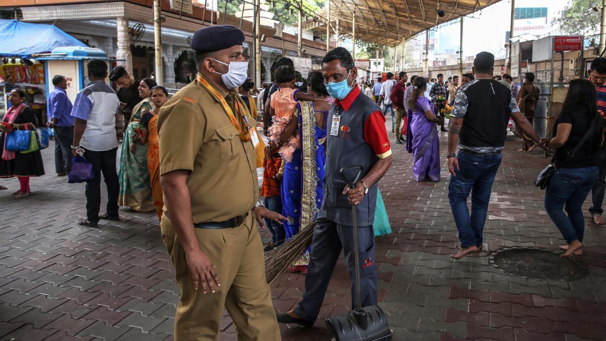 Ciudadanos de la India lucen mascarillas ante el aumento de casos en el país.