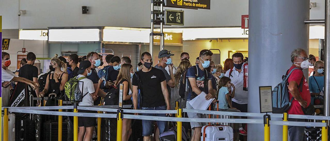 Colas de viajeros esperando para embarcar en el aeropuerto de El Altet estos días.  | ANTONIO AMORÓS