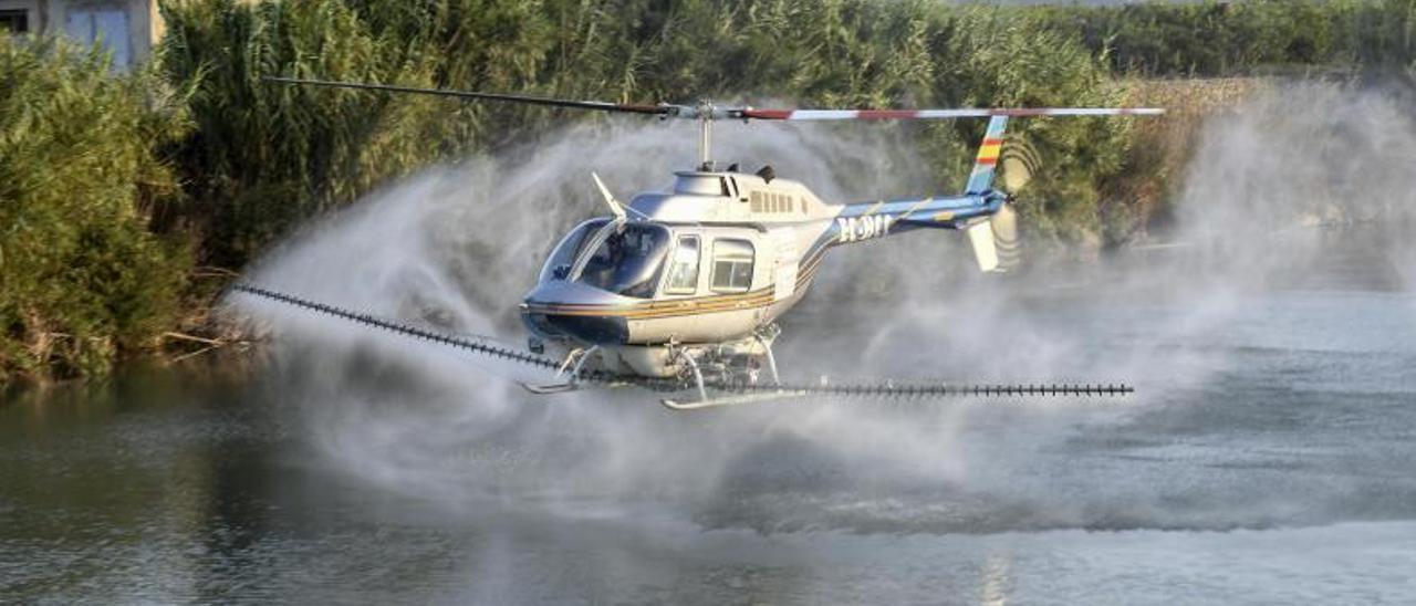 El helicóptero que aplica el tratamiento en las aguas del Xúquer, en una imagen de archivo. | XIMO FERRER