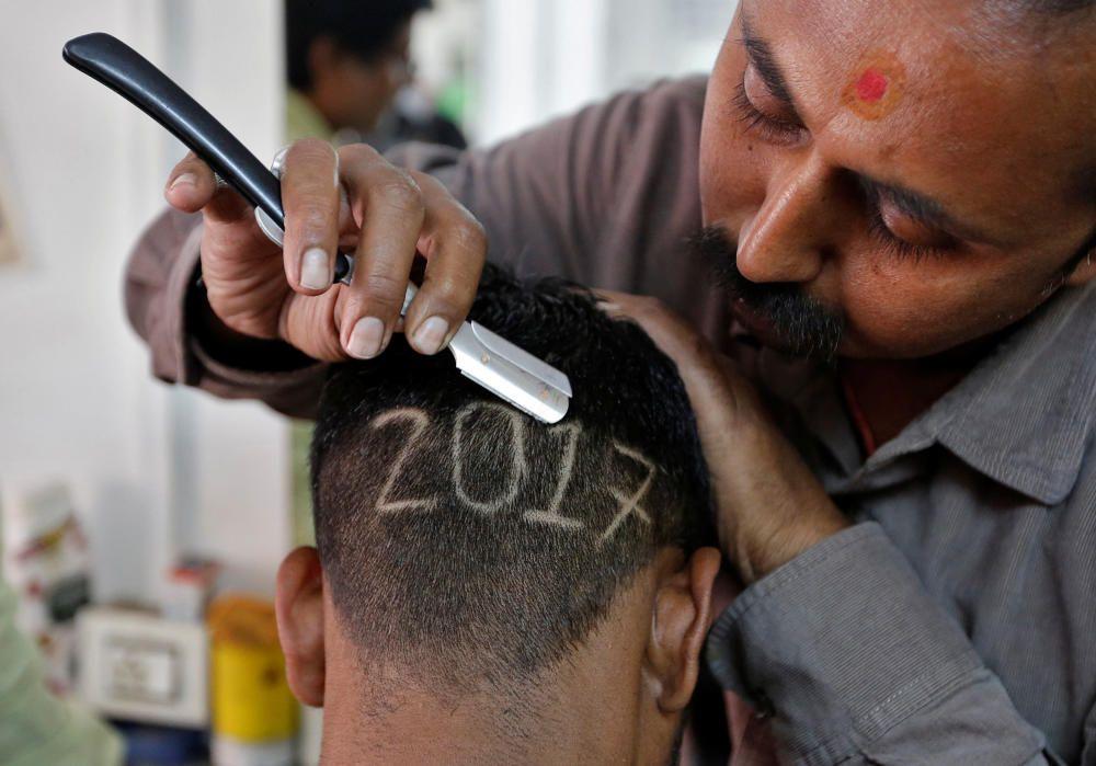 Un barbero 'escribe'en la cabeza de un cliente en Ahmedabad, India.