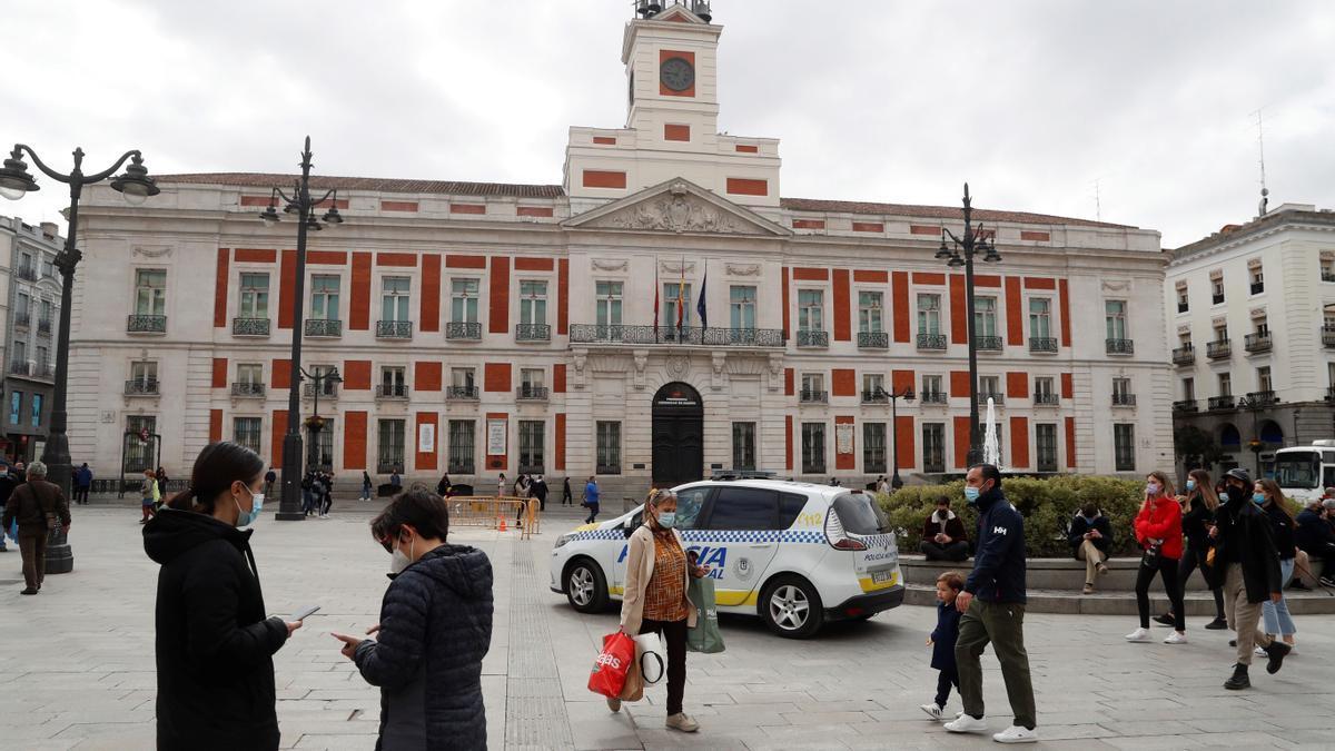 Un coche de la policía local circula entre los transeúntes que pasean por la Puerta del Sol