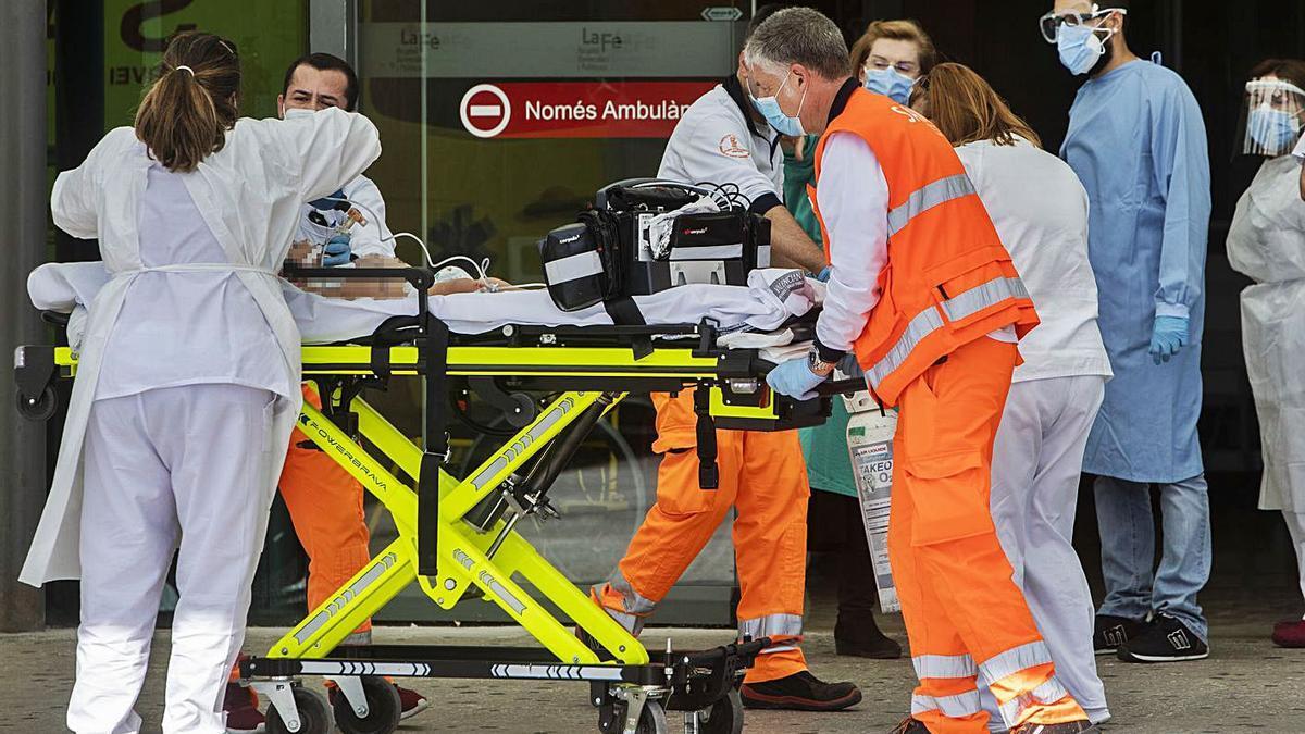 Sanitarios protegidos por equipos de protección en la puerta de urgencias de La Fe.  | GERMÁN CABALLERO