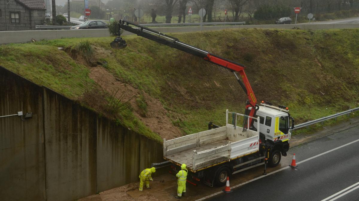 Operarios de Carreteras retiran el lodo de la N-640 a su paso por la rotonda de Baión