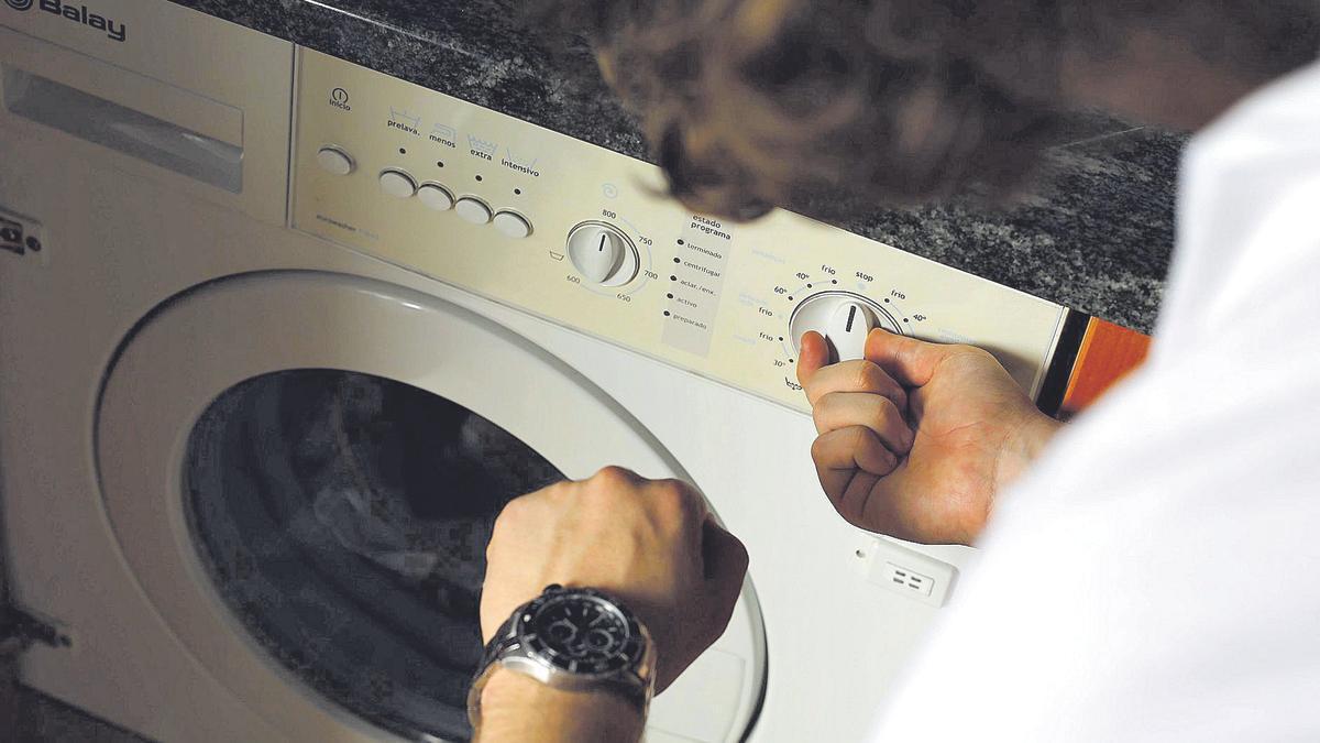 Un zaragozano pone a funcionar la lavadora de su casa mientras revisa la hora