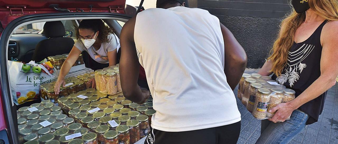 Tres voluntarios de Somos Red recogen alimentos donados en el bar Tiramisú. | | ANDRÉS CRUZ