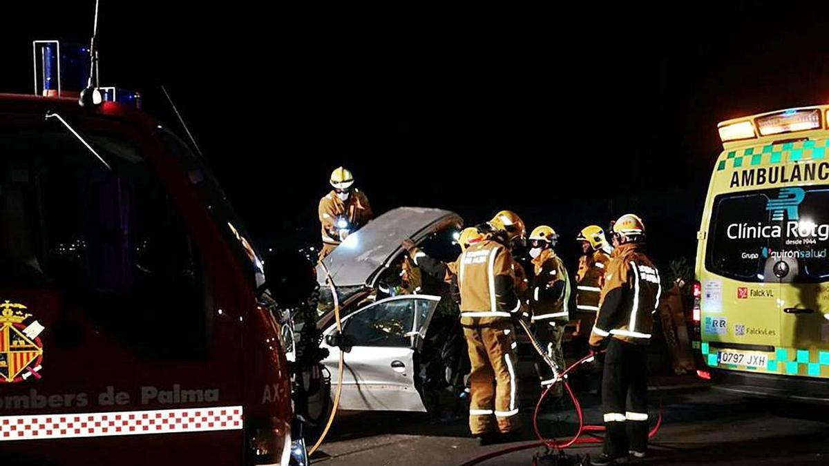 Varios bomberos trabajan para rescatar el cadáver de la anciana fallecida en el accidente.