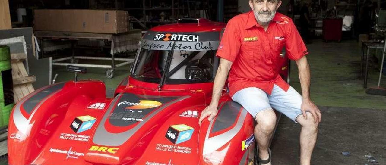 Jesús Bango, sentado sobre su coche último modelo BR53 en sus talleres de Valnalón, en Langreo.