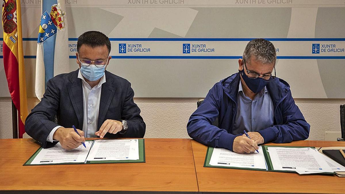 El conselleiro de Medio Rural y el vicepresidente de la Fundación Paideia, en la firma del convenio.     // L. O.