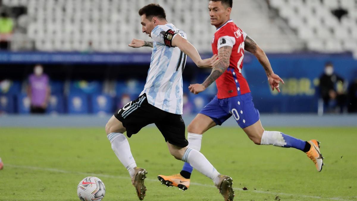 Leo Messi disputa un balón con Charles Aránguiz.
