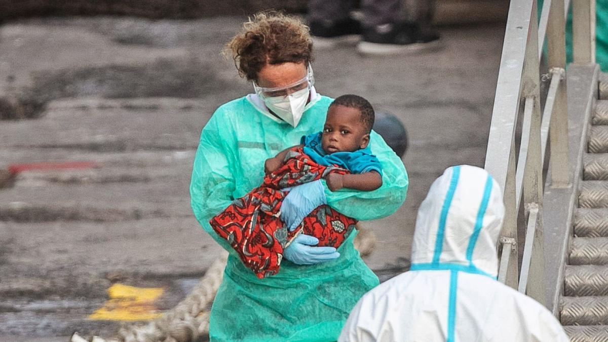 Una voluntaria de Cruz Roja se hace cargo de un bebé migrante que es auxiliado de Los Cristianos . | | ANDRÉS GUTIÉRREZ