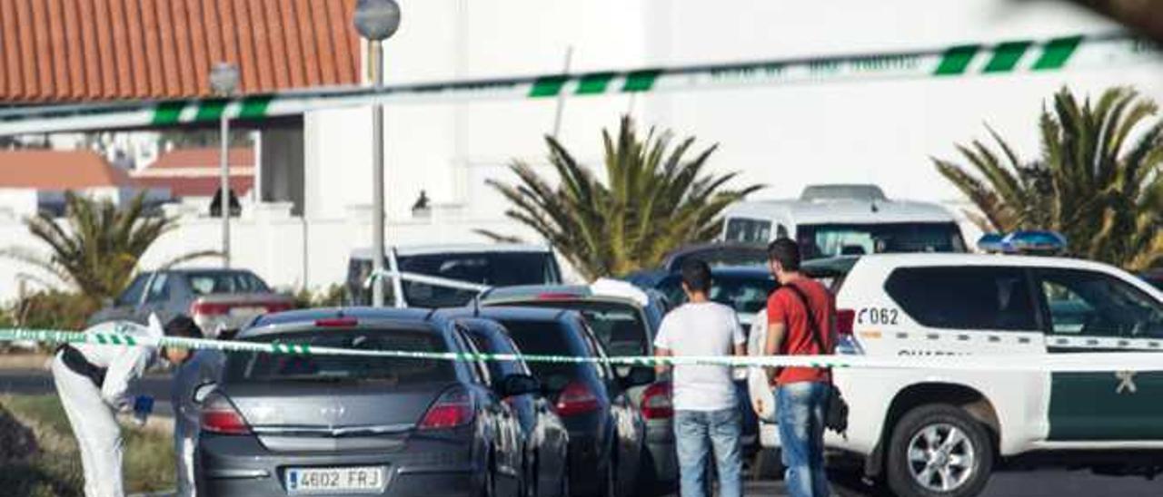 Un grupo de agentes de la Policía Nacional de la Guardia Civil analizando el coche del joven asesinado.