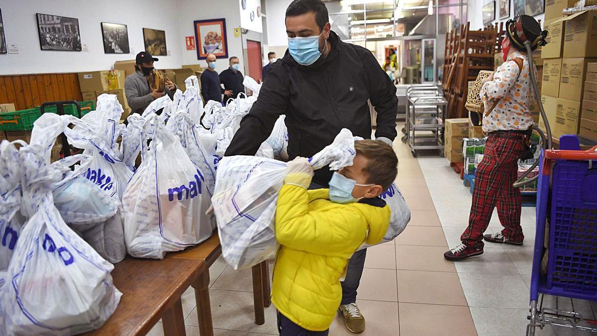 Dos voluntarios en una entrega de alimentos en la Cocina Económica.     // CARLOS PARDELLAS