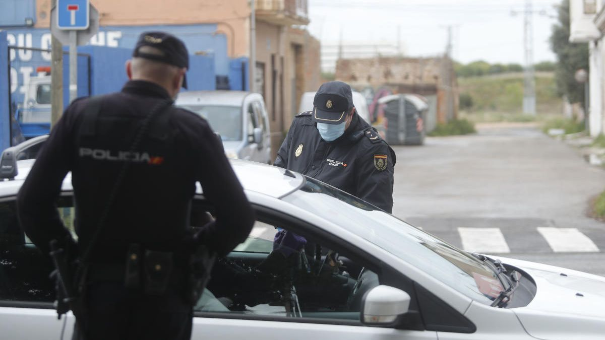 Dos policías nacionales piden la documentación a un conductor en un control en València.