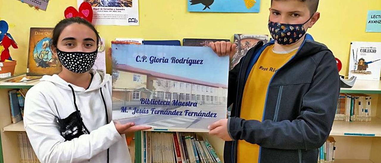 Lola Díaz López y Álvaro Alonso Suárez sostienen la placa que será colocada en la biblioteca del centro en recuerdo de María Jesús Fernández.