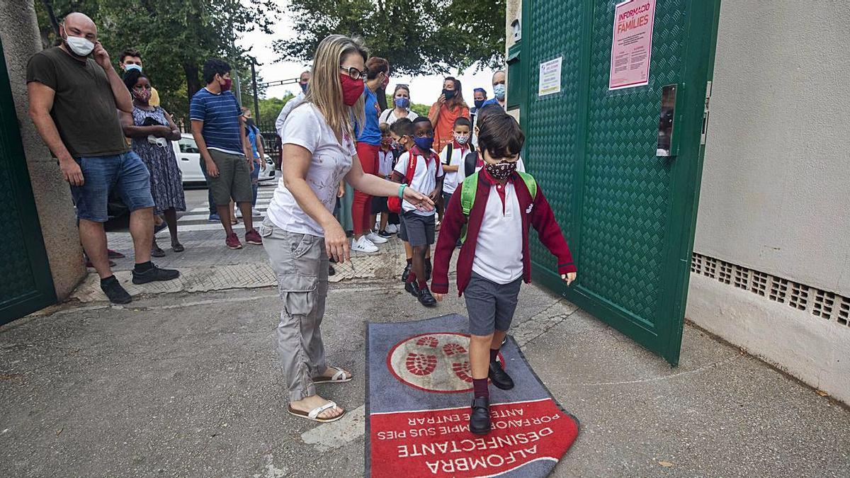 Un grupo de alumnos se desinfecta a la entrada de la escuela.