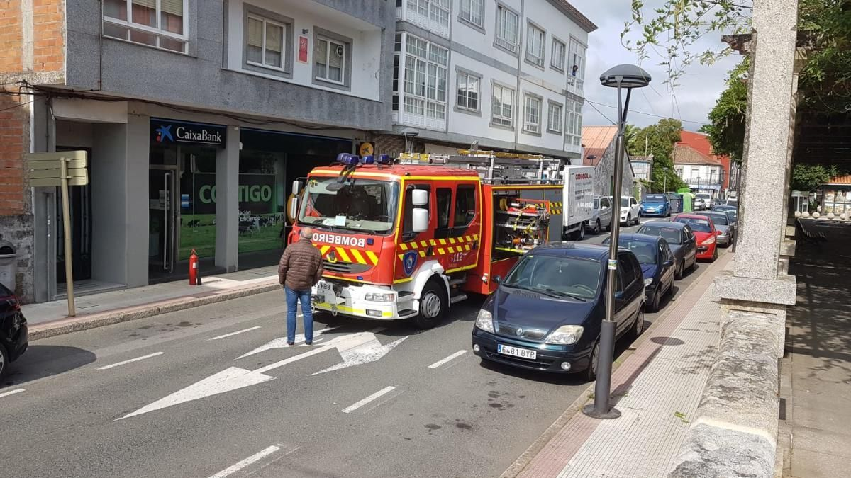 Un vecino observa el interior de la sucursal bancaria, con el coche de los bomberos en plena Avenida do Parque. // C.F.G.
