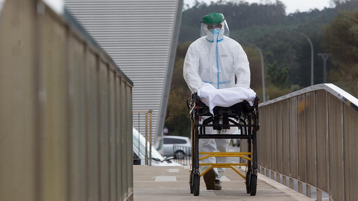 Un trabajador traslada una camilla en  la residencia  de San Cibrao afectada por la pandemia