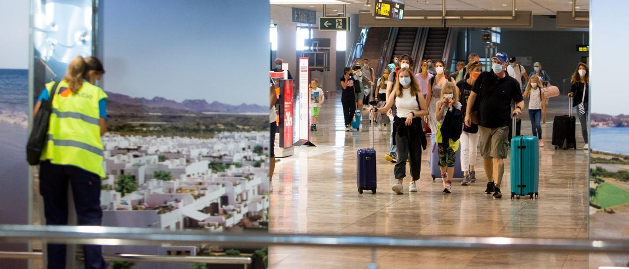 Turistas  con sus mascarillas caminan por la terminal del aeropuerto este pasado fin de semana.