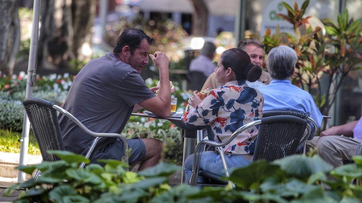 Dos personas hablan sentados en una cafetería.