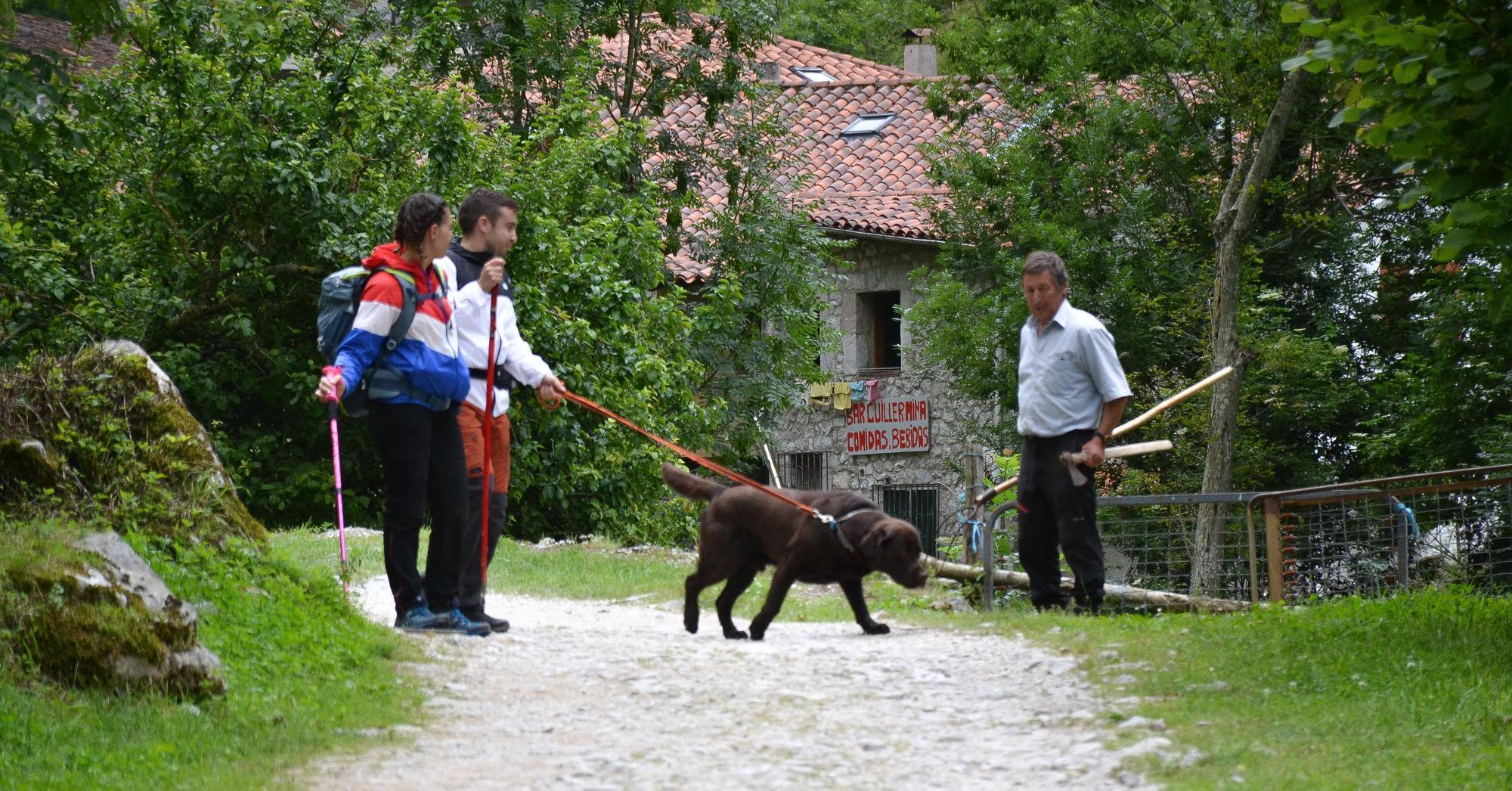 Dos jóvenes senderistas hablan con Falo Martínez, vecino de Bulnes.