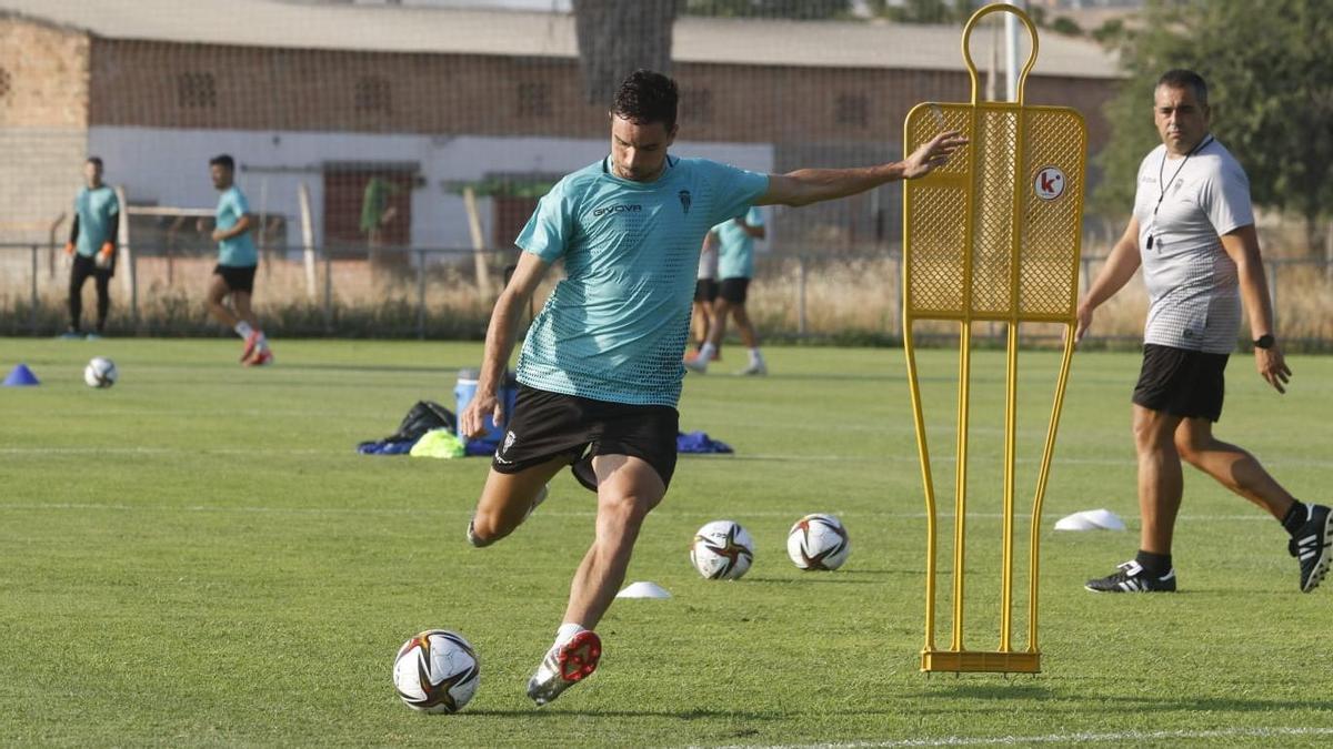 Toni Arranz dispara a portería bajo la atenta mirada de su entrenador, Germán Crespo, en un entrenamiento del Córdoba CF.