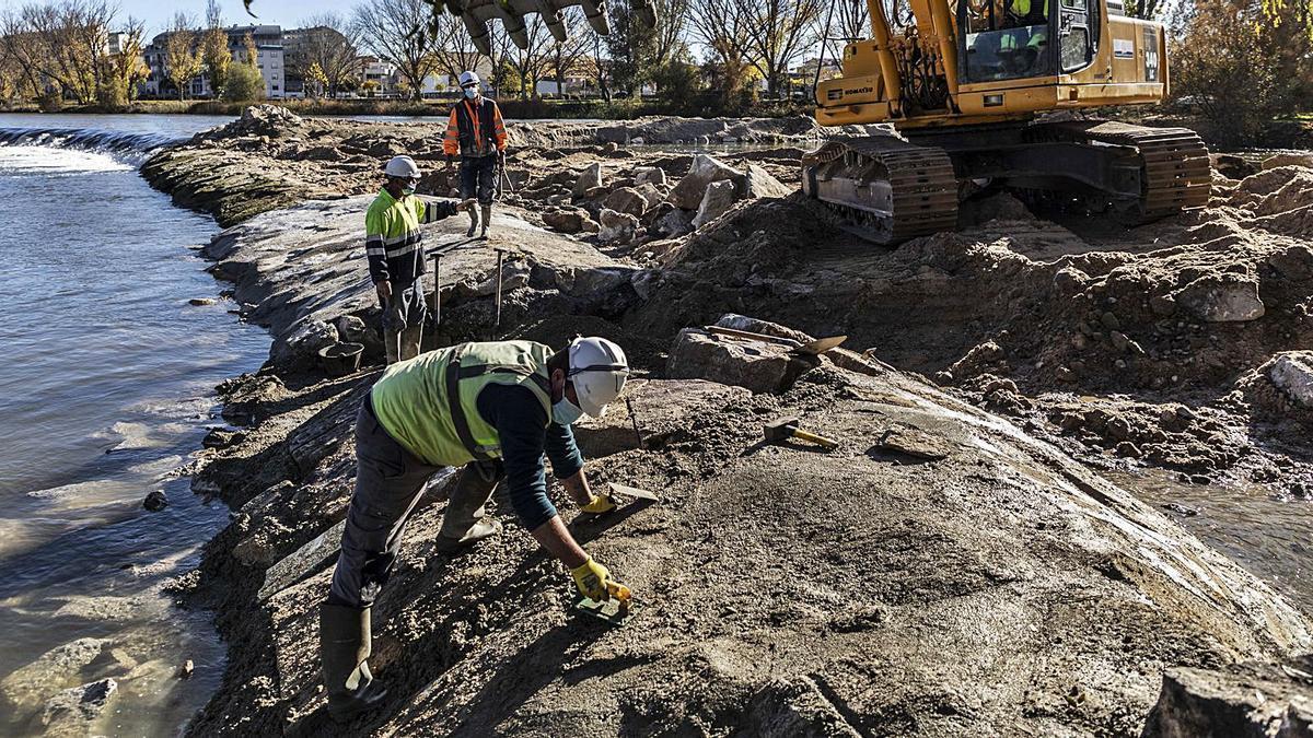 Los trabajadores actúan sobre la base del azud de Cabañales, en pleno cauce del río Duero.   Nico Rodríguez