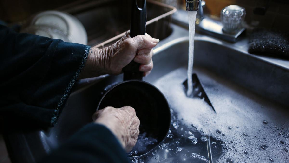 Un fregadero con el grifo de agua abierto y el usuario limpiando un utensilio.