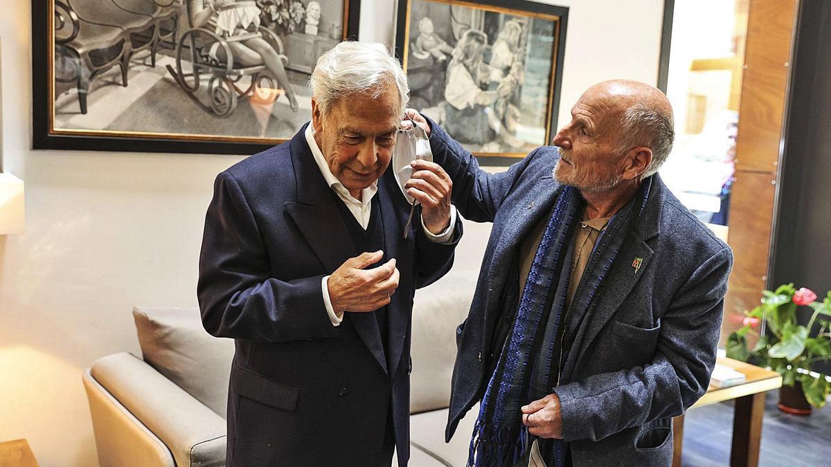 Antonio López (a la derecha) ayuda a quitarse la mascarilla al artista piloñés Félix Alonso, ayer, en el Colegio de Abogados de Oviedo.   Irma Collín
