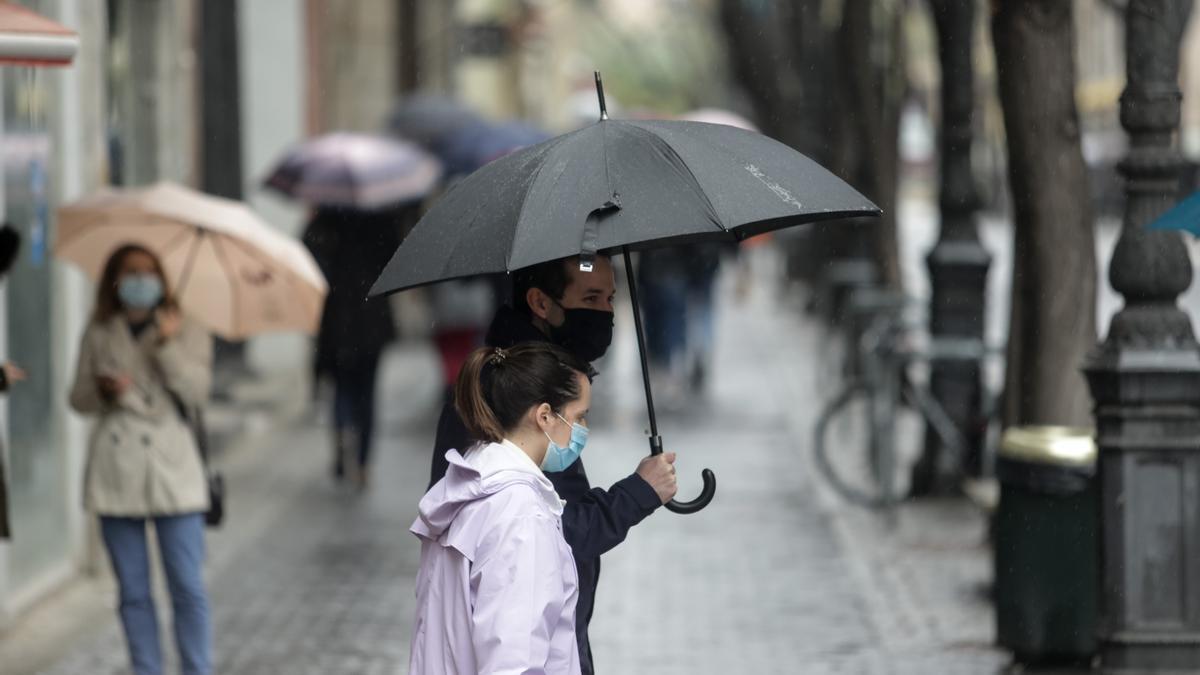 Dos valencianos pasean protegidos de la lluvia con un paraguas y del virus con sus mascarillas.