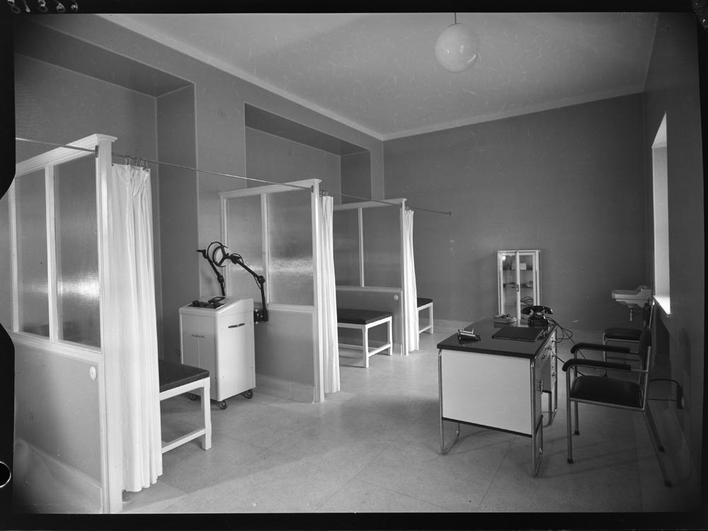 Sala de observaci�n con varias camillas separadas por biombos y mesa en frente.jpg
