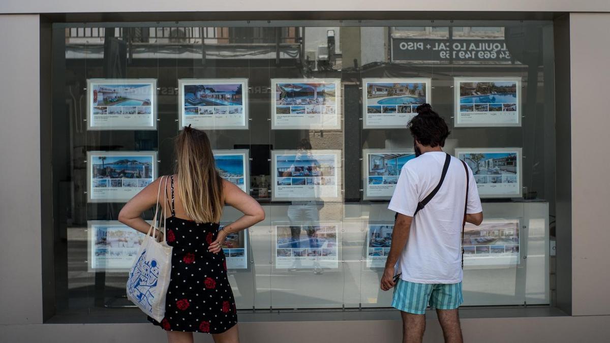 Archivo - Dos personas observan inmuebles en alquiler y en venta en un escaparate de una inmobiliaria ubicada en Palma