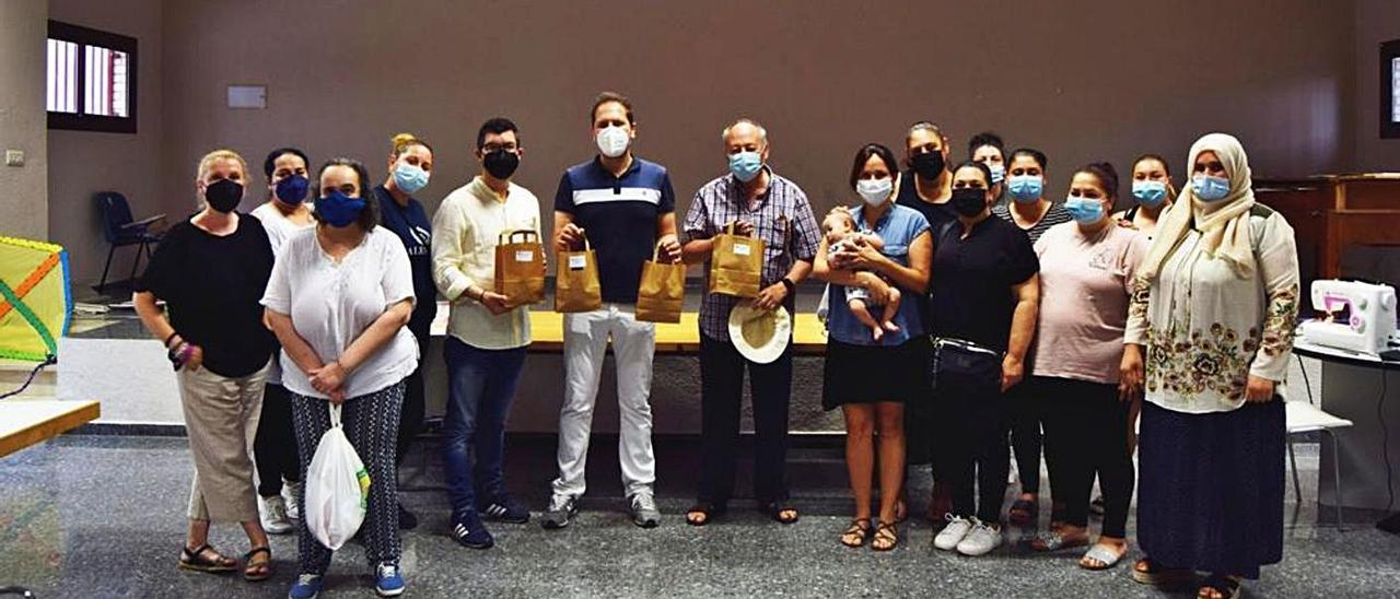 Las participantes en el curso de confección durante la entrega de las mascarillas al colegio.   A.T.