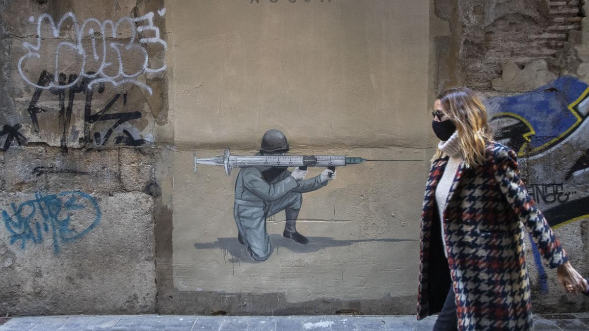 Un graffiti en València sobre la pandemia de coronavirus y las vacunas.