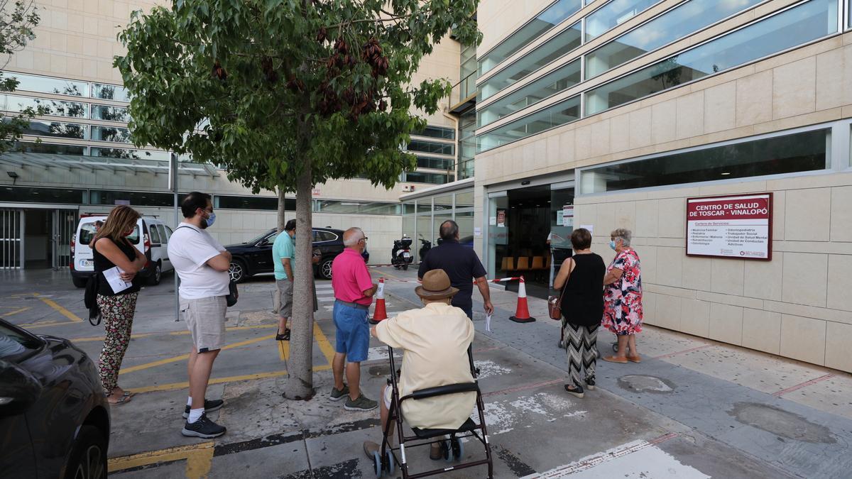Personas esperan ante el centro de Salud de El Toscar, gestionado por el Hospital del Vinalopó.