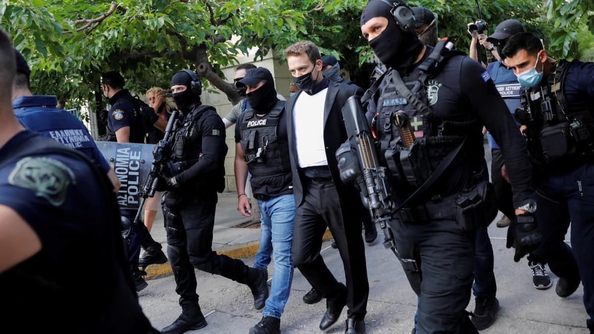 Un hombre de 33 años, que ha confesado haber asesinado a su mujer de 20 años, es escoltado desde la oficina del fiscal en un tribunal de Atenas (Grecia)